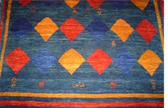 Basic Gabbeh feature a fairly coarse weave, with few knots per inch and a thick, plush wool pile. They usually have very little in the way of design elements, with large open fields, simple geometric shapes, bold, bright colors, and tribal drawings of people and animals.