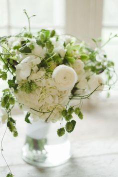 White hydrangea/rununcula with hops? Anyway, if you have a small water vessel on the cocktail tables the bridesmaids can pop their flowers in after wedding. Or have them line your table with the greenery around.