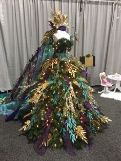 Peacock inspired Christmas Tree Dress...featuring a crown and 8foot lighted train! Fit for a princess! By A Ribbon Runs Through It #peacocktree #christmastree #dresstree