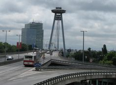"Novy Bridge (Novy Most or SNP Bridge) - crosses the Danube River in Bratislava, Slovakia;  designed by J. Lacko and A. Tesar;  the steel deck of the bridge is suspended from a single pylon;  the bridge is 431.8m long and 21m wide;  the ""flying saucer"" at the top of Novy Bridge (262 feet up) is a popular restaurant that features a spectacular view of the city;  the restaurant is connected to the bridge itself via an inclined high-speed elevator housed in one of the pylon's columns"