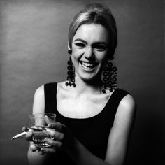 Edie Sedgwick. black and white photo 1966. her trademark chandelier earrings, drink and cigarette, black shift dress, black smokey eyeliner, dark eyebrows. Warhol Factory underground superstar young and happy, before all the drugs kicked in.