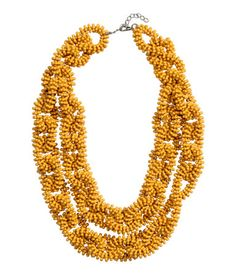 Yellow. Double-strand elastic necklace with small plastic beads. Adjustable…