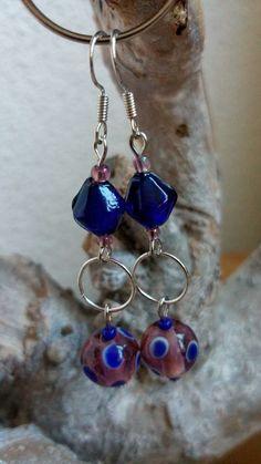 Kobaltblauwe bicone glaskraal met daaraan een ringetje. Daaraan hangt een paarse glaskraal met kobaltblauwe stippen.