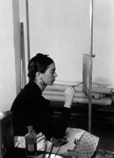 Frida Kahlo (1907-1954) mexican painter, here painting a Self-portrait on the border line between Mexico and United States in Detroit Institute of Art mural project studio, 1932.