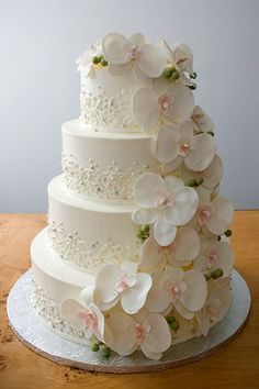 Elegant cascading orchids create a lovely focal point on this romantic cake with lace detailing and bits of bling.