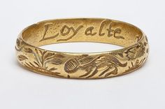 """This posy ring dates from the 17th century and was created in either Great Britain or France by an unknown maker. Animals and plants are engraved on the outer hoop, and there are traces of white enamel on the hare (front and center), suggesting it once was brightly colored. The inscription on the inside reads """"LOYALTE NE PEUR,"""" which translates to """"loyalty not fear."""""""