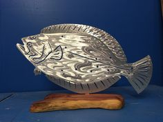 Flounder - Standing Mount  Using only the best local hardwoods found in South Florida. We hand craft & carve each base. First, we chainsaw, hand sand, polish and apply several coats of polyurethane to create a stunning standing mount or tournament trophy.  For more details visit https://themetaledge.com/trophies/flounder-standing-mount.html