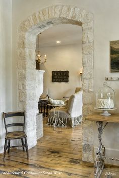 Love the arched stone doorway and rich looking wood floors.