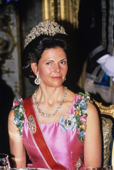 Queen Silvia of Sweden wearing the Braganza (or Bragança) tiara. Composed of arabesques, flowers, and leaves depicted in diamonds and mounted in gold and silver, this tiara measures just under 5 inches tall.