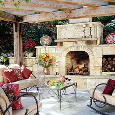 Mix Materials for a Stone Outdoor Fireplace  A wooden pergola shields this grand fireplace, which includes a rustic wooden mantel and an niche for storing wood. A collage of stones—large rectangles across the facade, narrow segments describing a flattened arch over the firebox, and mosaic tiles above the mantel—creates texture and visual interest