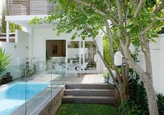 Quaint lap pool with a wood plank surround nestled in a small backyard.
