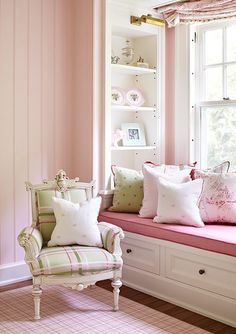 A wonderful living room sitting area in pink... white book shelves with a great pink bench for seating...
