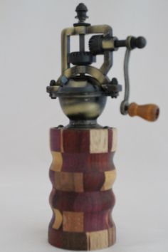 "This peppermill has an antique-style peppermill mechanism that adjusts easily from coarse to extra fine. The metal is an Antique Brass finish. It does not accommodate salt since it is metal. The body of the mill contains 120 pieces of exotic woods. It is approx. 2.5""dia. x 8""H. Cards for the Care of Wood and the names of all the woods and origin are sent with the purchase. # 623"