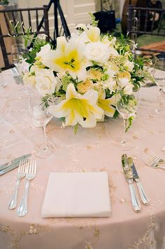 Large white and yellow lilies stand out among white roses.
