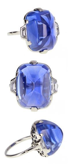 An Art Deco platinum, Ceylon sapphire and diamond ring, 1920s. Set to the centre with a sugar loaf Ceylon sapphire weighing 30 carats, mounted in six simple platinum claws and flanked on each side by a trapezoid diamond, the pierced gallery featuring scroll work with a slightly tapering shank.