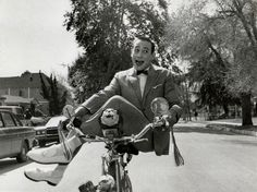Pee-wee Herman rides a bike, showoffily.