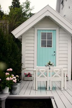 Look at this little shed on the back patio. I love the aqua door, the table and chairs and the tubs of flowers - yes, I love it all!