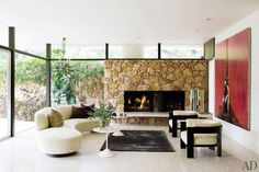 Designer Brad Dunning maintained a midcentury vibe with his renovation of Hollywood talent manager Eric Kranzler's 1957 home in Beverly Hills, California. He matched the living room fireplace to the house's stone façade and the wall bordering the pool area. (May 2011)