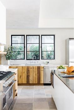 Sleek, minimalist kitchen with reclaimed wood cabinets and steal appliances