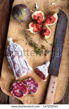 rustic plate with Salami, Ciabatta bread and fresh figs and an old knife, bird`s eye view - stock photo
