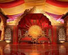 Gold and red decorated mandap for an opulent Indian wedding ceremony.  Complete with draped ceilings, intricate columns and gilded chairs.