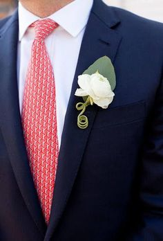 A classic white boutonniere comprised of a single overblown ranunculus created by Island Ambiance.