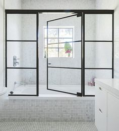 These steel framed windows and door give this shower a luxe, industrial edge and create a chic enclosure around the space #bathroom #shower #interiordesign #industrial