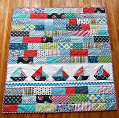Baby Gifties by cornbreadandbeansquilting: I didn't have time to go out and get a pattern because I wanted to start at 9 pm so I looked around on Pinterest for some inspiration.  I saw the cutest little baby quilt on there.  I drew up a sailboat block and used stash to come up with something similar. I zipped up some (sorta) straight line quilting, and bound it in red and white stripes. Quick and simple.