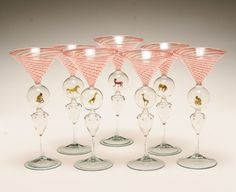 """Seven Bimini Werkstatte martini glasses, Vienna, 1930's. Double knop stem, the upper enclosing various animals such as giraffes, monkeys, etc., the lower of triangular form with drop prunts. 7 1/2""""H. Good condition."""