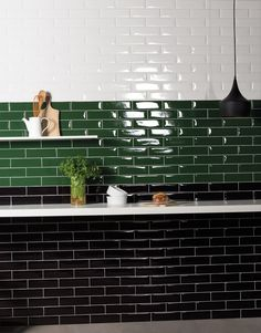 Green, black and white subway tiles on this stunning kitchen wall