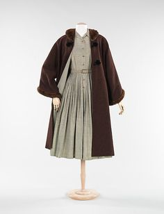 Taupe silk shirtwaist dress with matching belt and brown wool coat with fur trim, by Vera Maxwell, American, ca. 1954. The shirtwaist dress is an iconic look of the fifties, which Maxwell has executed well with this ensemble. Her choice of Harris Tweed for the jacket is no surprise, as she promoted the use of tweeds in all of her collections. A Maxwell touch, she often lined her jackets with the dress fabric, bringing a sense of harmony to the ensemble.