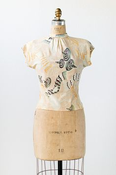1940s novelty toursit print blouse. This top feaures a high mandrin collar, short dolman sleeves, and button closures down the back center. There is ultra flattering seam detail at the waist. The top is a light peach color with a colorful novelty print throughout.
