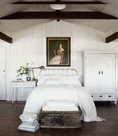 Railroad trestles were installed as beams in this rustic bedroom. A flea market oil portrait watches over the antique iron bed, covered with Pottery Barn's fisherman-knit blanket.