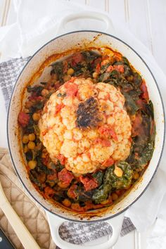 This Whole Braised Cauliflower with Chickpeas, Tomato, and Kale is the perfect one-pot vegan dinner. Created by The Grateful Grazer.
