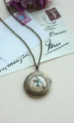 Bird and Bicycle Locket Necklace. Round Antiqued Brass