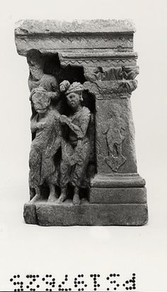 Part of a corner panel showing worshippers. A monk, face lost, his right arm wrapped in his robe, his left arm pendent, stands beside a male in a crested turban, hands joined, wearing a paridhāna, an uttarīya in the narrow mode, a collar, necklace and earrings. Above the monk a damaged half-length figure with a collar joins his hands. All are probably turned towards the lost Buddha