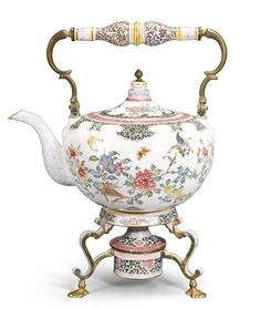 A CANTON ENAMEL KETTLE AND BURNER QING DYNASTY, EARLY 18TH CENTURY brightly enamelled overall with butterflies and other insects in flight amongst leafy branches issuing large floral blooms including peony, morning glory and camellia, interspersed with fruiting sprays of the sanduo, all reserved on a an opaque white ground, divided by ruyi-shaped lappets and floral scrolls, the cover and the burner similarly decorated  32.5cm., 12 3/4 in.
