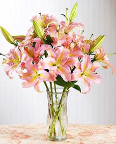 6 pink perfume lilies in a clear glass vase