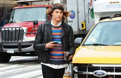 Groovy dude with patterned sweater and headband. Don't forget cell. Love.