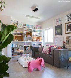 Sala de estar com estante branca com nichos de madeira pinus, sofá cinza e elefante da marca Vitra.