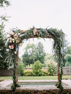 Wooden Ceremony Arbor Decorated with Flowers and Greenery | Brides.com