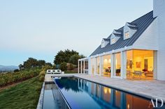 The rear of this house by Jacobsen Architecture opens onto the travertine-tiled terrace and an infinity pool.