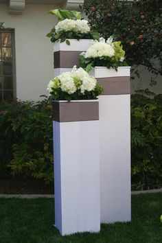 Good for a backdrop to a ceremony in a garden or somewhere that has no focal point - tall box towers with florals on top