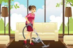 Ella limpia el piso de su casa de el polvo con el aspirador.