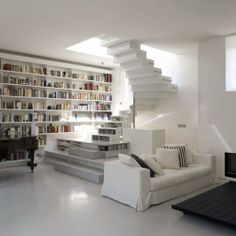 A unique loft in Paris featuring a winding staircase with built-in bookshelves!