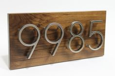 Clean steel lettering mounted on standoffs on a contrasting wooden plaque