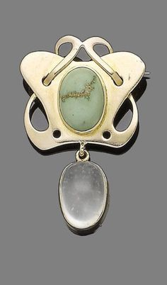 An art nouveau turquoise and moonstone brooch, circa 1910.  The openwork abstract plaque, centrally-set with an oval cabochon turquoise, suspending an oval cabochon moonstone, length 4.8cm, fitted case by P. Vaughton & Sons, Gothic Works, Birmingham
