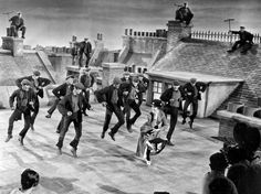 """Actress Julie Andrews dances with the chimney sweeps in the chimney-sweep dance number during filming of """"Mary Poppins"""" on a movie set representing London rooftops at the Disney Studios in Hollywood, Ca. Julie Andrews Mary Poppins, Mary Poppins Movie, Mary Poppins 1964, Walter Elias Disney, Smokey And The Bandit, Today In History, Historical Images, Disney Movies, Movies"""