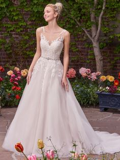 Olivia Wedding Dress | Rebecca Ingram. A lace bodice and illusion bateau neckline add romance and enchantment to this tulle ballgown. A unique illusion lace back features cascading keyholes, while a Swarovski crystal-embellished belt adds a touch of sparkle. Finished with covered buttons over zipper closure.