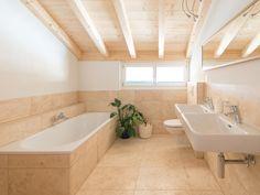 Die warme Farbgebung der Travertin-Fliesen sorgt für die einladende Wirkung dieses Badezimmers – jonastone